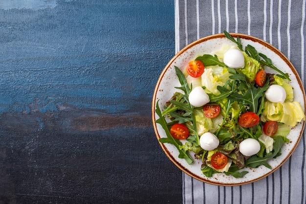 Sałatka z serem mozzarella, rukolą, sałatą i pomidorami widok z góry