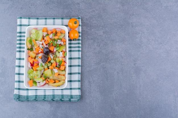 Sałatka z sezonowymi ziołami i warzywami na półmisku