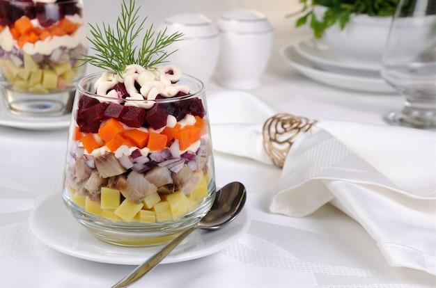 Sałatka z siekanego śledzia z cebulą ziemniaki buraczki marchew doprawione sosem jogurtowym w szklance