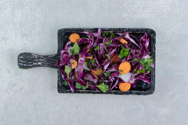 Sałatka z siekanych warzyw w drewnianej desce, na marmurowym tle.