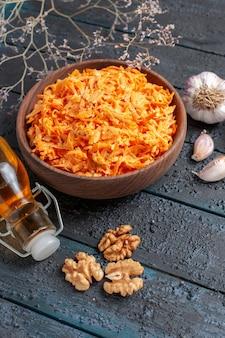 Sałatka z tartej marchewki z czosnkiem na ciemnoniebieskim rustykalnym biurku sałatka zdrowa warzywa kolor dieta dojrzała
