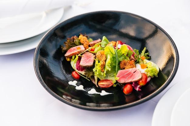 Sałatka z tuńczyka średniego rzadziej (zielony koral, czerwony koral, pomidor i łosoś) z dotykanym czesakiem na czarnym talerzu.