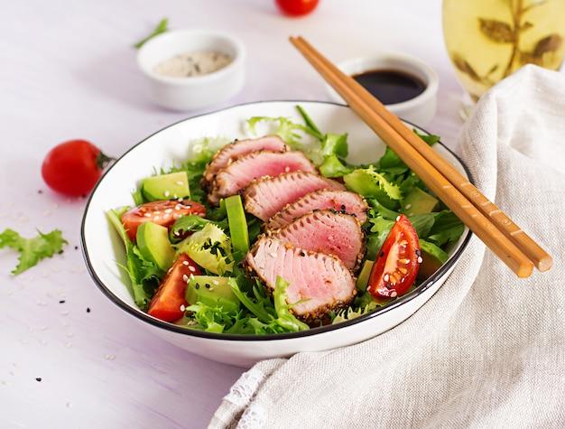 Sałatka z tuńczyka. tradycyjna japońska sałatka z kawałkami średnio rzadkiego grillowanego tuńczyka ahi i sezamu ze świeżym warzywem na misce.