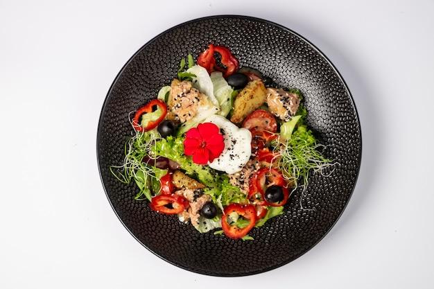 Sałatka z tuńczyka w połączeniu ze smażonymi ziemniakami, papryką, oliwkami, jajkiem w koszulce, na poduszce z mixem sałat i dressingiem na bazie dwóch musztard, na białej powierzchni