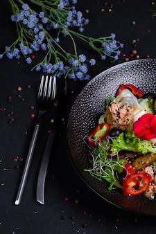 Sałatka z tuńczyka w połączeniu ze smażonymi ziemniakami, papryką, oliwkami, jajkiem w koszulce, na poduszce z mixem sałat i dressingiem na bazie dwóch musztard, na ciemnej powierzchni