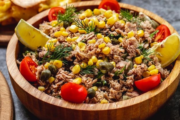 Sałatka z tuńczyka z boczkiem i kaparami marynowanymi w słodkiej kukurydzy, pomidorem koperkowym i plasterkiem cytryny w drewnianej misce