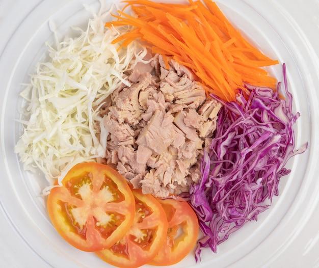 Sałatka z tuńczyka z marchewką, pomidorami, kapustą na białym talerzu na drewnianej podłodze.