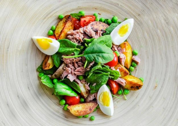 Sałatka z tuńczyka z sałatą, jajkiem i pomidorami na drewnianym talerzu