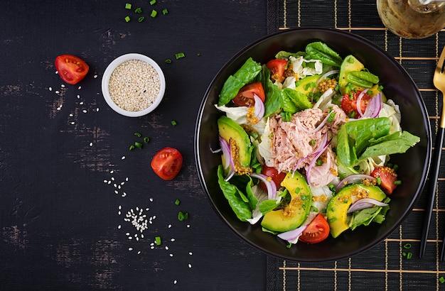 Sałatka z tuńczyka z sałatą, pomidorkami koktajlowymi, awokado i czerwoną cebulą. zdrowe jedzenie. kuchnia francuska. widok z góry, miejsce na kopię, płaski układ