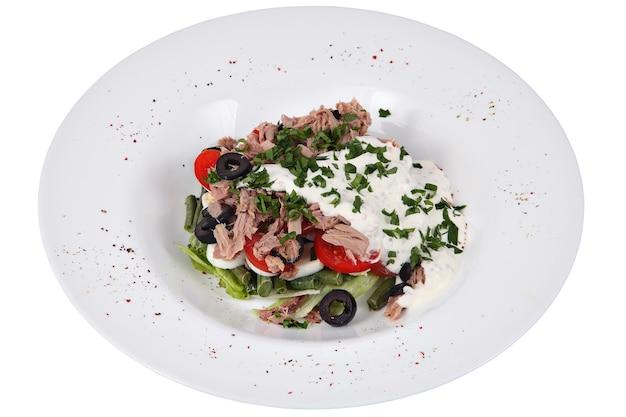 Sałatka z tuńczyka z zieloną fasolką, sałatą, pomidorami i oliwkami na okrągłej białej płytce na białym tle.
