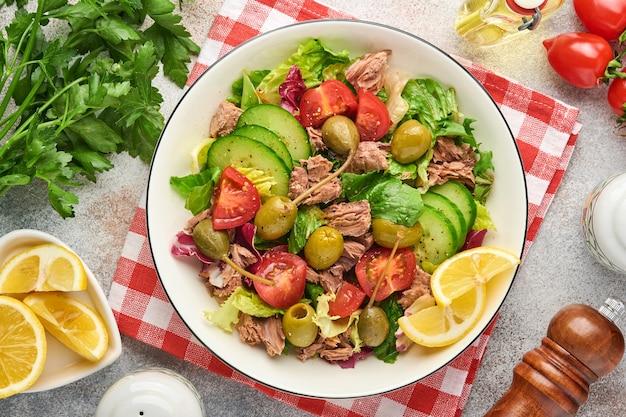 Sałatka z tuńczyka ze świeżymi warzywami, oliwkami, kaparami i cytryną podawana w misce na jasnoszarym tle. widok z góry z miejsca na kopię.
