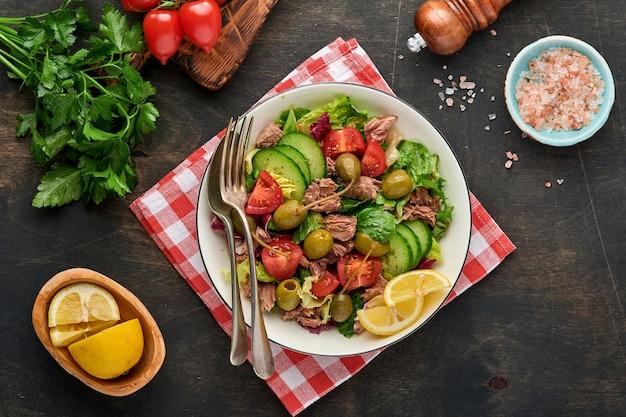 Sałatka z tuńczyka ze świeżymi warzywami, oliwkami, kaparami i cytryną podawana w misce