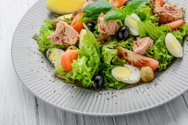 Sałatka z tuńczykiem z pomidorami, oliwkami, jajkami i cebulą.