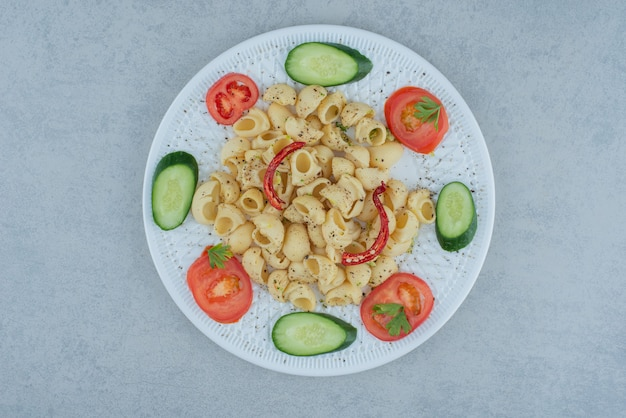 Sałatka z warzyw na białym talerzu z pysznym makaronem na tle marmuru