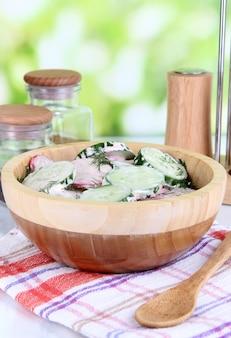 Sałatka z warzyw witaminowych w drewnianej misce na drewnianym stole