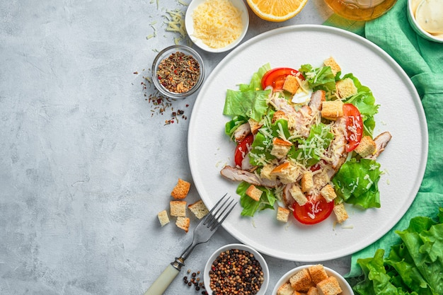 Sałatka z warzywami i piersią kurczaka na szarym tle. tradycyjna sałatka cezar. pojęcie zdrowego odżywiania.