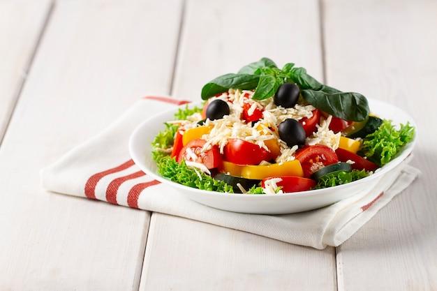 Sałatka z warzywami i serem, na białym talerzu nad ściereczką kuchenną na białym drewnianym tle