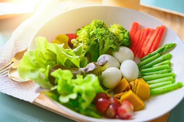Sałatka z warzywami i zieleniną na drewnianym stole