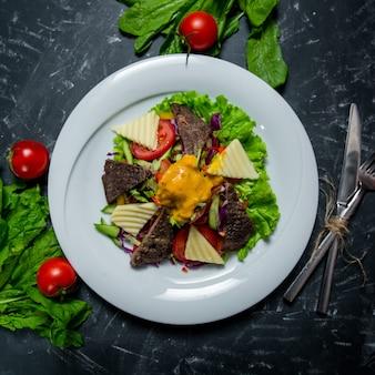 Sałatka z warzywami na białym talerzu z pomidorami i srebrnymi sztućcami dookoła na ciemnym tle