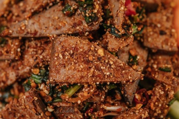 Sałatka z wątróbki wieprzowej z chili, pieczonym ryżem, szczypiorkiem, marchewką i ogórkiem.