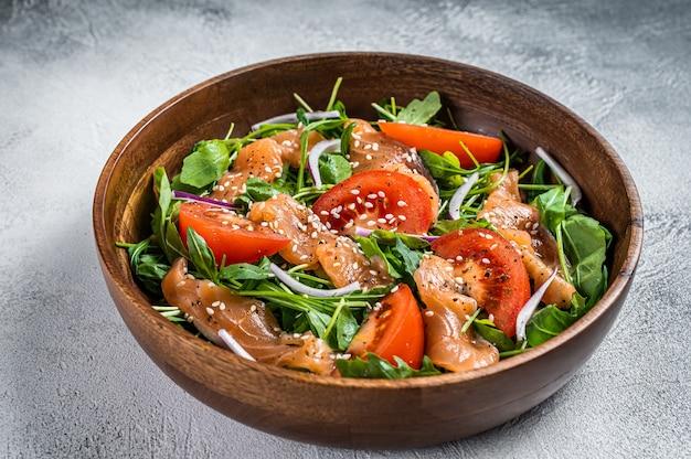 Sałatka z wędzonego łososia z rukolą, pomidorem i zielonymi warzywami. biały stół. widok z góry.