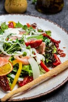 Sałatka z wędzonym łososiem, sałatą, suszonymi pomidorami i sosem serowym, obraz pionowy. widok z góry,