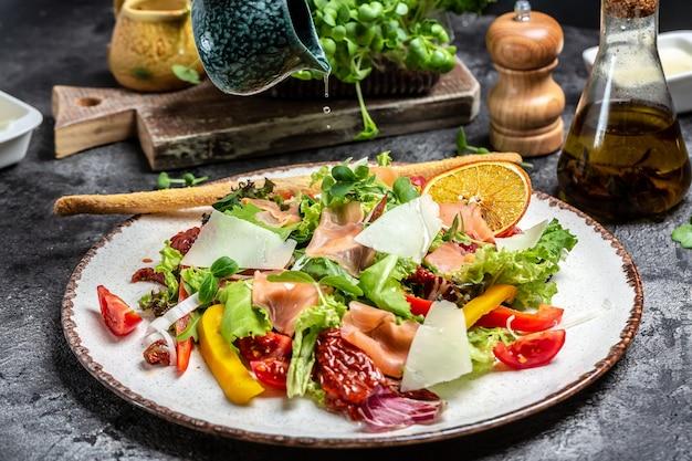 Sałatka z wędzonym łososiem z sałatą, suszonymi pomidorami i ziołami, pyszna zbilansowana koncepcja żywności
