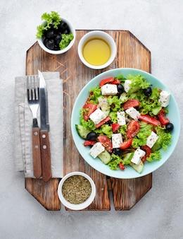 Sałatka z widokiem z góry z serem feta na desce do krojenia z oliwkami i ziołami