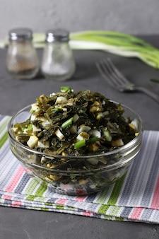 Sałatka z wodorostami, jajkiem i zieloną cebulką w przezroczystej misce na szarym tle. format pionowy