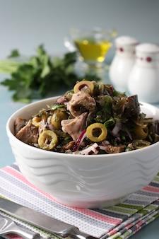 Sałatka z wodorostami, tuńczykiem w puszkach i oliwkami w białej misce na jasnoniebieskim tle. format pionowy. zbliżenie