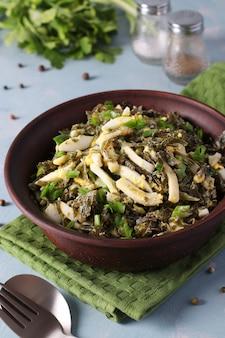 Sałatka z wodorostów, kalmarów i zielonej cebuli w brązowej misce na jasnym tle.