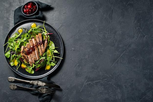 Sałatka z wołowina stkiem, arugula i chard na czarnym talerzu.