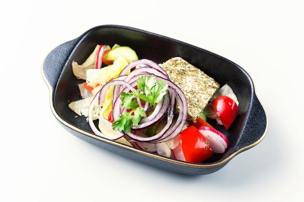Sałatka z zdrowych organicznych warzyw z rzodkiewki, szpinaku, pomidorów, cebuli i ogórka w misce na białej powierzchni. widok z góry.