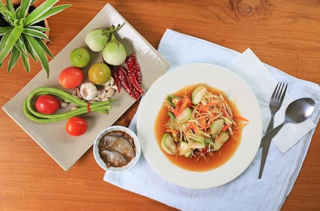 Sałatka z zielonej papai z marynowanymi rybami na białym talerzu na tle drewnianego stołu. widok z góry