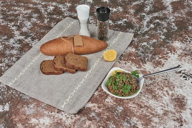 Sałatka z zielonej soczewicy z kromkami chleba.