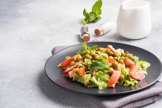 Sałatka z zielonych liści pomidora i groszku konserwowego doprawiona sosem na czarnym talerzu. świeża sałatka dietetyczna wiosenna. skopiuj miejsce.