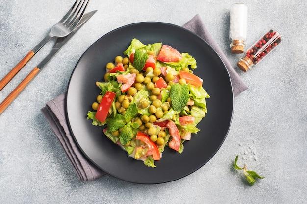 Sałatka z zielonych liści pomidora i groszku konserwowego doprawiona sosem na czarnym talerzu. świeża sałatka dietetyczna wiosenna. widok z góry