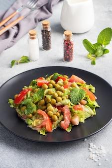 Sałatka z zielonych liści pomidora i groszku konserwowego doprawiona sosem na czarnym talerzu. świeża sałatka dietetyczna wiosenna.