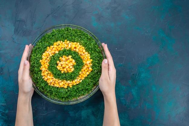 Sałatka z zielonych warzyw z widokiem z góry na okrągłym szklanym talerzu na ciemnoniebieskim biurku.