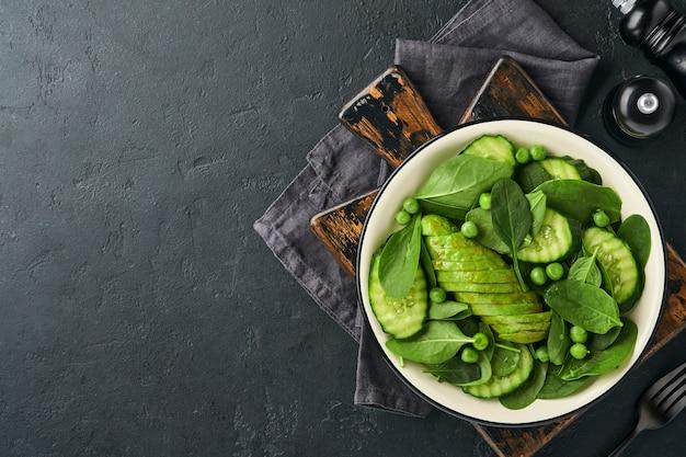 Sałatka z zielonych warzyw ze szpinakiem, awokado, zielonym groszkiem i oliwą w misce na ciemnym łupku