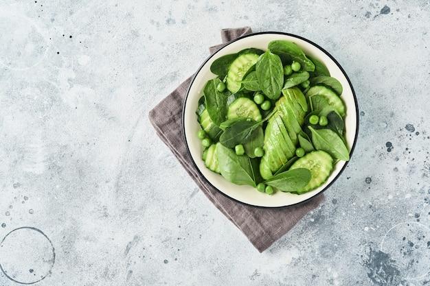 Sałatka z zielonych warzyw ze szpinakiem, awokado, zielonym groszkiem i oliwą w misce na jasnoszarym łupku