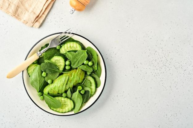 Sałatka z zielonych warzyw ze szpinakiem, awokado, zielonym groszkiem i oliwą w misce na jasnoszarym tle łupkowym, kamiennym lub betonowym. widok z góry z miejsca na kopię. zielone warzywa dla koncepcji diety.