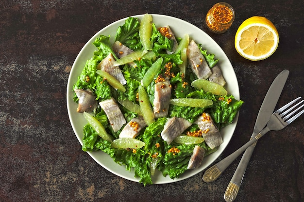 Sałatka ze śledziem i filetem z cytryny. dieta paleo, dieta keto, dieta pegańska. zdrowa sałatka fitness z cytryną i rybą.