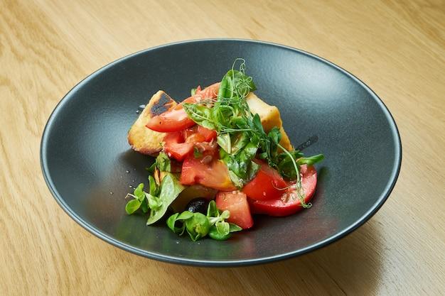 Sałatka ze smażonymi pomidorami koktajlowymi z sera halumi i mikrogreenem w czarnej misce na drewnianym stole. jedzenie w restauracji
