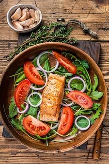 Sałatka ze steków z łososia z rukolą z zielonych liści, awokado i pomidorem na drewnianym talerzu. drewniane tło. widok z góry.