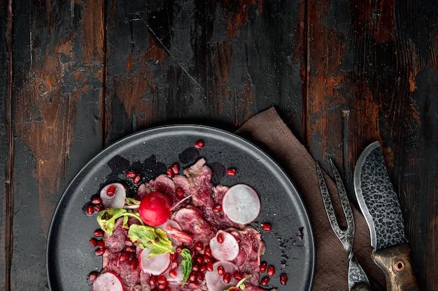 Sałatka ze świeżego carpaccio z octem winnym, rzodkiewką i granatem, na talerzu, na starym ciemnym drewnianym stole