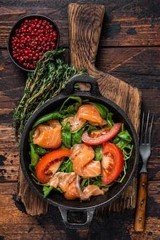 Sałatka ze świeżego łososia z rukolą, pomidorem i zielonymi warzywami. ciemne drewniane tło. widok z góry.
