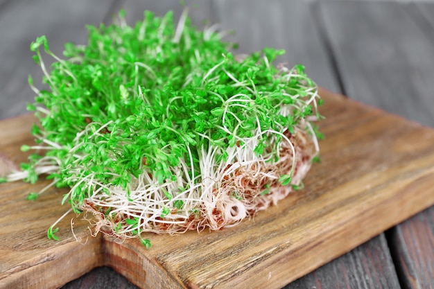 Sałatka ze świeżej rzeżuchy na desce do krojenia i drewnianych deskach