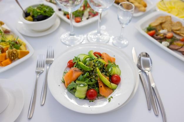 Sałatka ze świeżej sałaty jagnięcej z awokado, ogórkiem, łososiem, pomidorkami koktajlowymi. dressing z miodem, musztardą dijon, oliwą z oliwek i sokiem z cytryny, posypany nasionami chia. przygotowane przez szefa kuchni.
