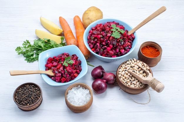 Sałatka ze świeżych buraków z pokrojonymi warzywami wewnątrz niebieskich talerzy ze składnikami na lekkim biurku, sałatka jarzynowa jedzenie posiłek przekąska zdrowotna